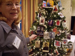 Carol placing a picture of her Dad on tree